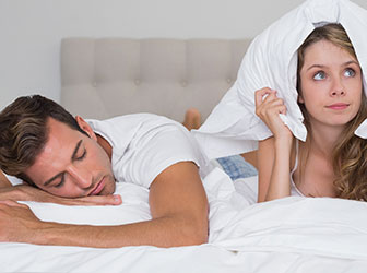 Couple wearing white laying in bed