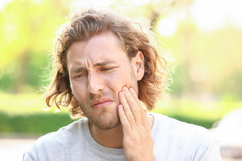 Closeup of young man suffering with toothache