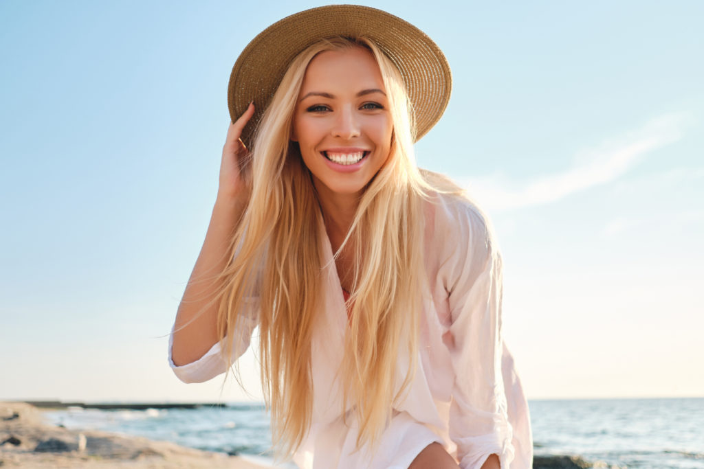 Woman with white, straight teeth smiling on the beach