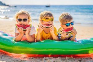 three kids eating watermelon on the beach to prevent dental emergencies
